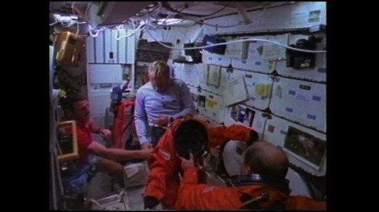 UNITED STATES: 1980s: astronauts put on entry space suits.