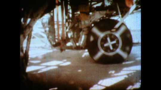 United States: 1980s: Test wheels spin in research. Water sprayed on moving wheels. Close up of aircraft wheels landing on wet runway.