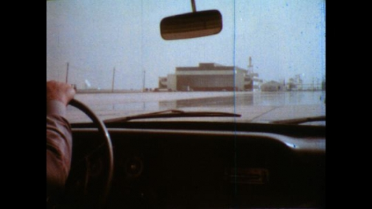United States: 1980s: View from inside of car as driver travels across wet surface. View from side as car travels over wet surface.