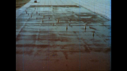 United States: 1980s: Car travels through obstacle course on wet surface. Car hits cones.
