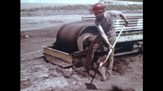 UNITED STATES: 1980s: man digs by machine. Worker clears machine with pole. Man slips.
