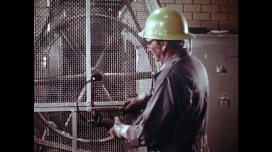 UNITED STATES: 1980s: man tests pressure on machine. Man positions drill bit. Man closes guard door.