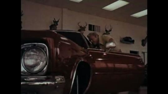 1970s: Man closes car door, zoom in, man talks into camera.