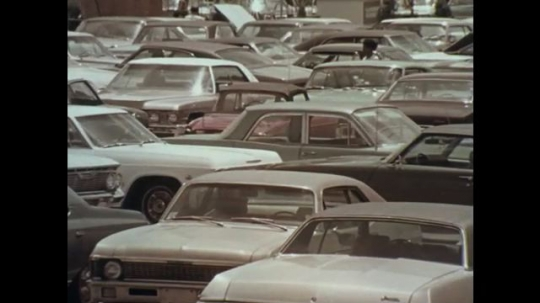 1970s: Pan across cars in parking lot / Zoom in on building entrance / Dissolve, car parts on conveyor belt / Cans moving in machine.