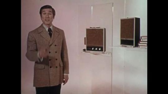 1970s: Man next to radios, talks into camera / Radios / Dissolve, close up pan of radio / Close up of radio / Close up of radio / Close up of cassette / Tilt up stack of cassettes.