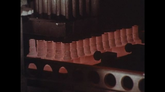 1970s: Spark plugs in machine / Close up of spark plugs / Cars on highway / Cars on highway / Spark plugs light up / People walking / Sign, zoom out, man opens poster / Air filters on conveyor belt.