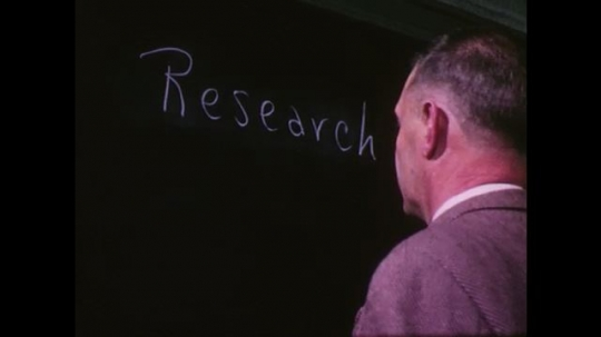 UNITED STATES 1950s: man writes Research and Educ on blackboard with chalk. Teenage boys write in notebooks with pencils.