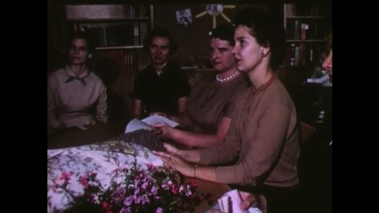 UNITED STATES 1950s: women at table compare fabric swatches. future farmers of america banner. man talks to teenage boys in field.