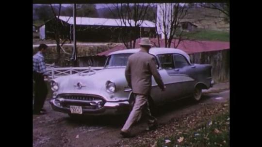 UNITED STATES 1950s: man and teenage boy get inside 1955 Oldsmobile car. 1955 Oldsmobile car drives off farm. men weigh bushel baskets of vegetables on scale. man weighs bale of cotton.