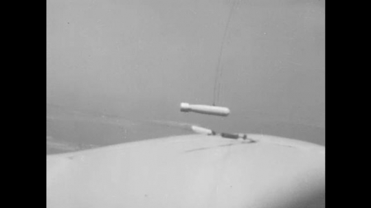 canister flies through air with cable. airplane tows canister by cable.