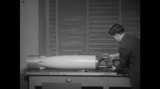 man examines missile on table. hands examine monitoring magnetometer device on tip of missile.