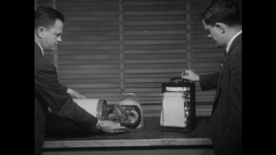 man sets magnetometer device in canister. man points out printer readout. man guides screwdriver over magnetometer device. man points readout levels on printer. hands show readout levels on printer.