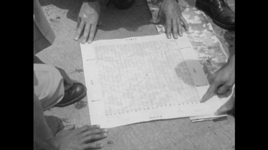 hands examine map. finger points out map grids.