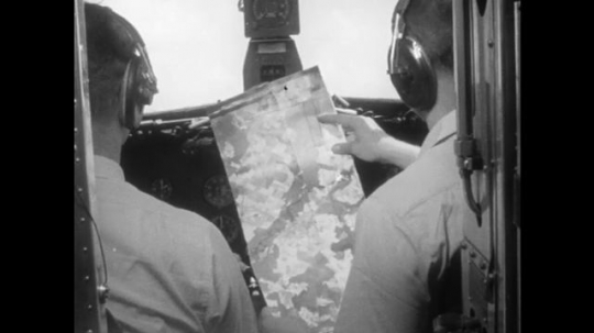 men review map in airplane cockpit. farm and forest. men review map in airplane cockpit. Man speaks into microphone. man writes on clipboard. man checks counters.