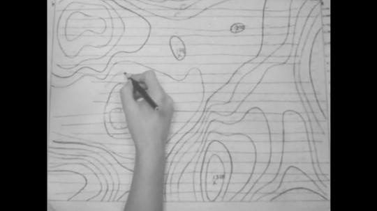 hand draws line on topographic map. woman draws line on topographic map.