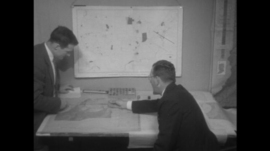 men examine map on table. men point at maps on table. men point at map on wall.