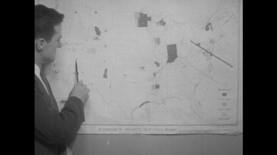 man points at map on wall. man leans on table to point at map on wall. men look at map on wall. airplane tows canister in the air.