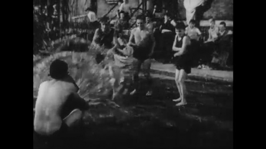 UNITED STATES: 1950s: children play in fire hydrant spray on street.  Adults ride bicycles.