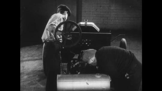 UNITED STATES: 1950s: men build Ford motor car. Ford pulls vehicle past men.