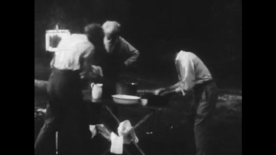 UNITED STATES: 1950s: Henry Ford goes camping with friends John Burrows and Harvey Firestone. Henry Ford swings axe.