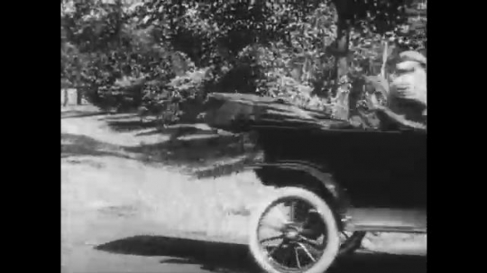UNITED STATES: 1950s: Man drives Ford Motor car. Men enjoy breakfast on camp site