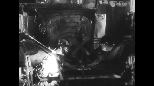 UNITED STATES: 1950s: Model T cars scrapped in factory. Car in crusher.