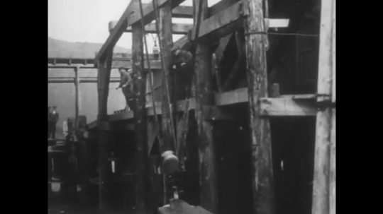 ALASKA: 1930s: boat comes in to harbour. Gulls above water an boat. People wait on jetty. Boy on jetty