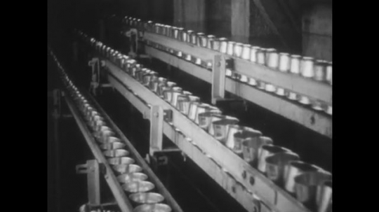 ALASKA: 1930s: cans on cannery machine. Cans on conveyor belt. Hands place fish into machine.