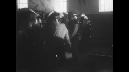 ALASKA: 1930s: men work in can processing factory. Men unload doors of machine
