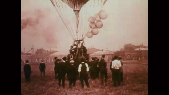 1890s: Men gather and jog around hot air balloon as it ascends. Mobile models of airplane wings twirl. Hanging model airplane wing twirls.