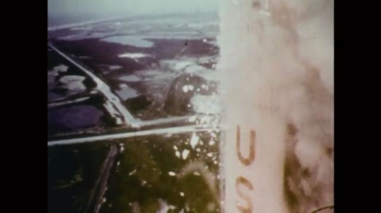 1960s: Side of rocket in takeoff. Smoke above river and title card.1900s: Men running with airplane.