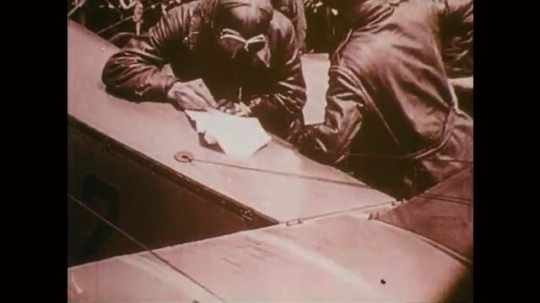 1918: Two pilots lean on plane, one writes on paper, crowd behind. Hands hold addressed, stamped envelope. President Wilson talks to woman and hands off piece of mail. Men load parcels into airplane.