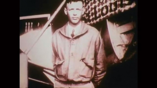 1920s: Lindbergh stands at attention. Title card. Men talk, work around airplane wing, one on top. International newsreel. Pilots talk by plane. Newsreel documents takeoff. Plane takes off, onlookers.