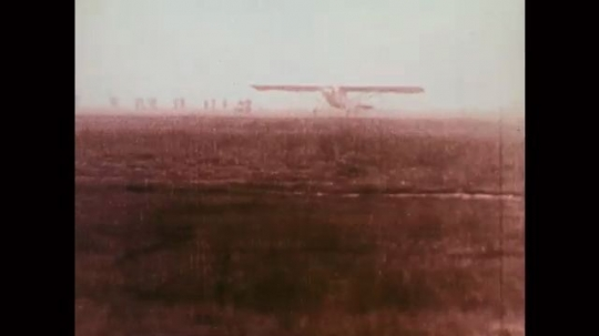 1920s: Airplane wobbles as it takes off over field, leaves ground.