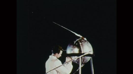 1950s: Man adjusts satellite parts. Light orbits planet. Parts of satellite break apart in space. Model of spinning satellite.