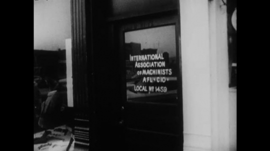 UNITED STATES: 1960s: Shop door sign: International Association of Machinists. Man enters shop. Employees leave through employees entrance