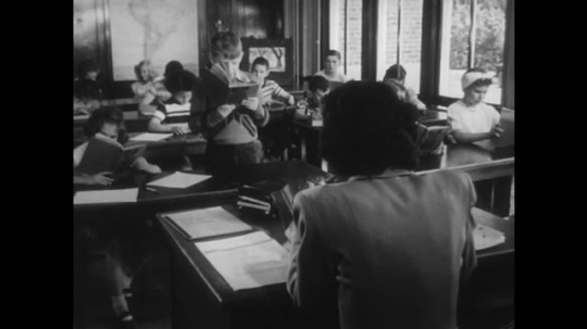 1950s: Boy stands reading to class and teacher. Students pack things into desks and start to leave room. Boy steals a classmate