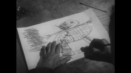 1950s: Boy makes drawing. Boy leaves drawing on desk and sits down. Man picks drawing up. Man speaks to boy.