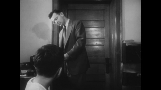 1950s: Man, standing, speaks to boy who is seated. Man carries paper to boy, hands it to him. Man sits with boy and looks at picture of a woman opening a door to a boy and policeman.