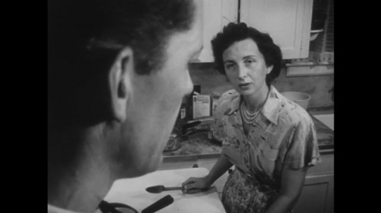 1950s: Man and woman stand in kitchen talking. Woman has utensil in hands. Man looks conflicted. Man stands in doorway with newspaper under arm, touches stove for emphasis while talking.