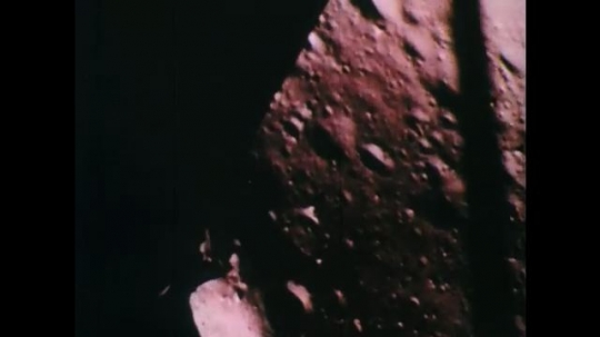 1960s: UNITED STATES: space capsule travels above surface of moon. Capsule lands on moon