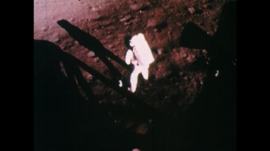 1960s: UNITED STATES: astronaut on moon collects samples of rocks