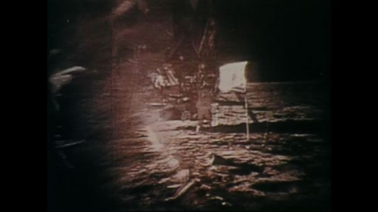 1960s: UNITED STATES: astronaut walks across surface of moon