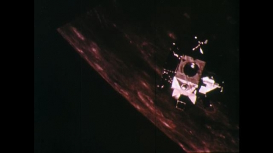 1960s: UNITED STATES: Space module flies above moon. Capsule rotates ins pace.