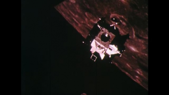 1960s: UNITED STATES: space capsule above surface of moon