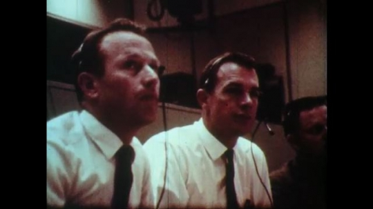 1970s men in white shirts and black ties wear headsets and point at screens in mission control. man smokes pipe and watches video from space.