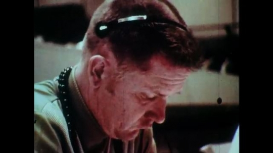 1970s man in headset looks down. men write notes on paper in mission control. men talk and read manual in space capsule. man shaves in zero gravity.