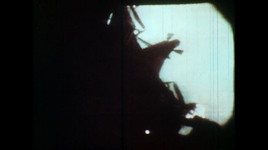 1970s lunar module separates from command module in space and descends to moon surface.