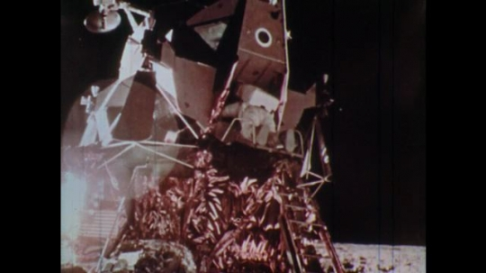 1970s man exits lunar module door and steps onto the moon surface.