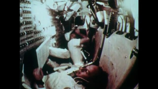 1970s men float around cockpit and read clipboard in command module. equipment left on the moon surface.